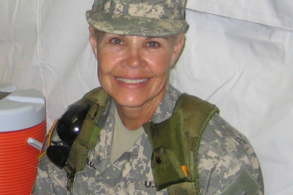 Sandra Carter, U.S. Army Retired smiles at the camera as she sits in uniform with a backpack on.