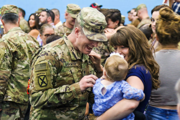 Soldier greeting his wife and daughter inside Monti Physical Fitness Center during the second Welcome Home ceremony for Soldiers of 2nd Brigade Combat Team, 10th Mountain Division returning from a nine month deployment, July 15, 2019, at Fort Drum, New York.