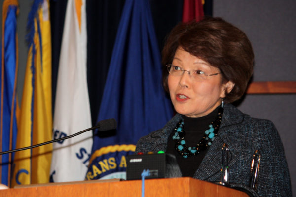 Mrs.Shinseki speaks over a podium at a conference.