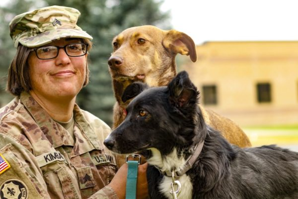 Sgt. Corina Kimball, an intelligence noncommissioned officer from Great Falls, Montana, with the 652nd Regional Support Group, sits with her dogs