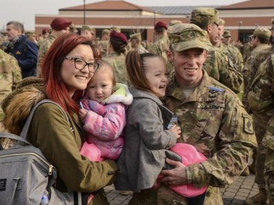 """""""My Daddy is the greatest!"""" A proud family congratulates a paratrooper who has just been awarded his Expert Infantryman Badge, as she is held at a ceremony at the 173rd Airborne Brigade."""